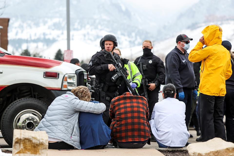 Police guard people who were evacuated after reports of an active shooter at the King Soopers grocery store in Boulder, Colo., on Monday. (Michael Ciaglo/USA Today Network via Reuters)