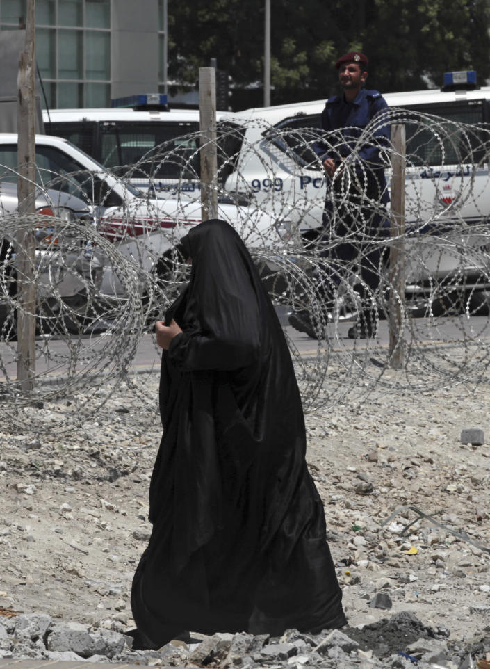 A Bahraini woman passes through an area being blocked off by police with razor wire to separate a village from a main road on the outskirts of Manama, Bahrain, on Tuesday, Aug. 13, 2013. Bahraini authorities are stepping up security ahead of plans announced by the anti-government opposition to launch a major rebellion Wednesday against the Gulf monarchy. (AP Photo/Hasan Jamali)