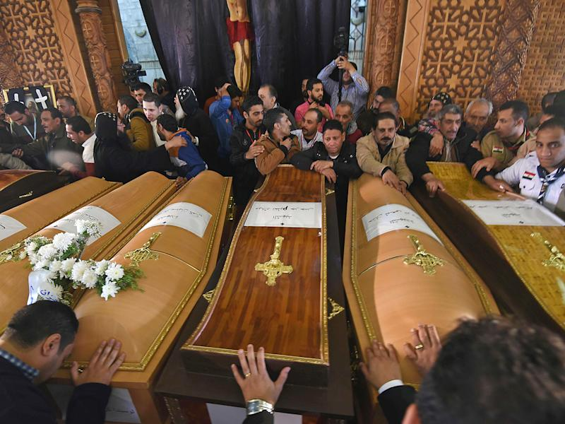Mourners pray next to coffins of victims of the blast at the Coptic Christian Saint Mark's church in Alexandria: Getty Images