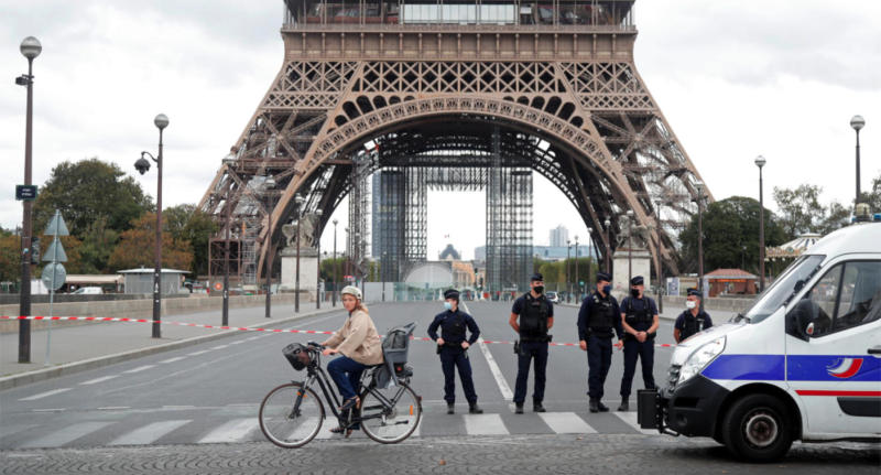 Police stand in front of the Eiffel Tower, blocking access to the structure while a woman on a bicycle rides past.