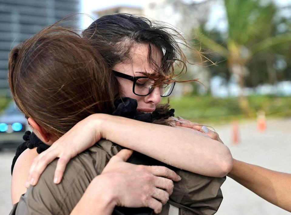 From left to right, Fayzah Bushnaq and Maria Fernanda Martinez comfort each other next to the Champlain Towers South Condo in Surfside, Florida, Friday, June 25, 2021. The apartment building partially collapsed on Thursday, June 24.