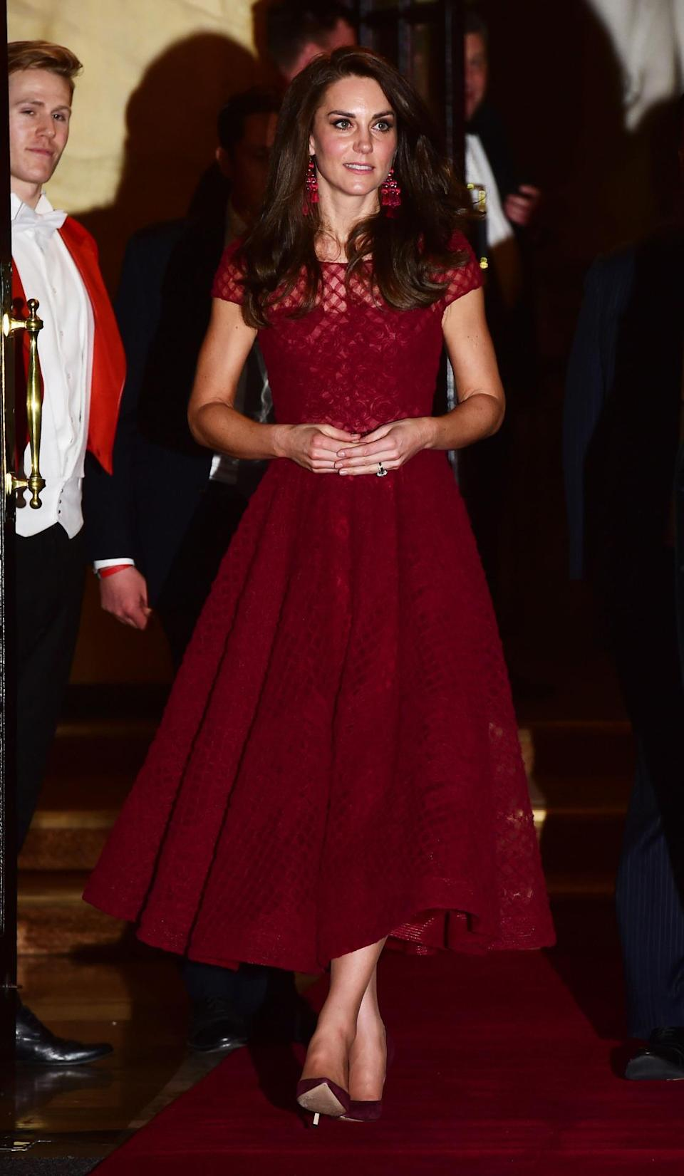 <p>Kate donned the colour of the season for the opening night of West End musical, <i>42nd Street</i>. Wearing a claret midi-length dress by Marchesa Notte (that cost £1,105), the Duchess opted for some seriously fashion-forward accessories including a pair of pom pom statement earrings from Kate Spade. Gianvito Rossi pumps and a matching Mulberry clutch topped off the look. </p><p><i>[Photo: PA]</i></p>