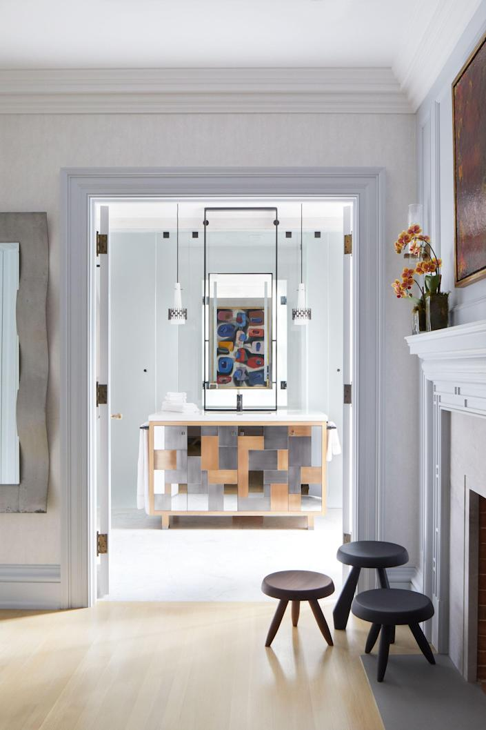 Symmetry is the focus of the primary bath, seen here at a distance. The vanity, which is framed by pendants from Austria, and the medicine cabinet, are perfectly centered between the shower and water closet. Both the vanity and medicine cabinet were designed in-house by Katherine Newman Design.
