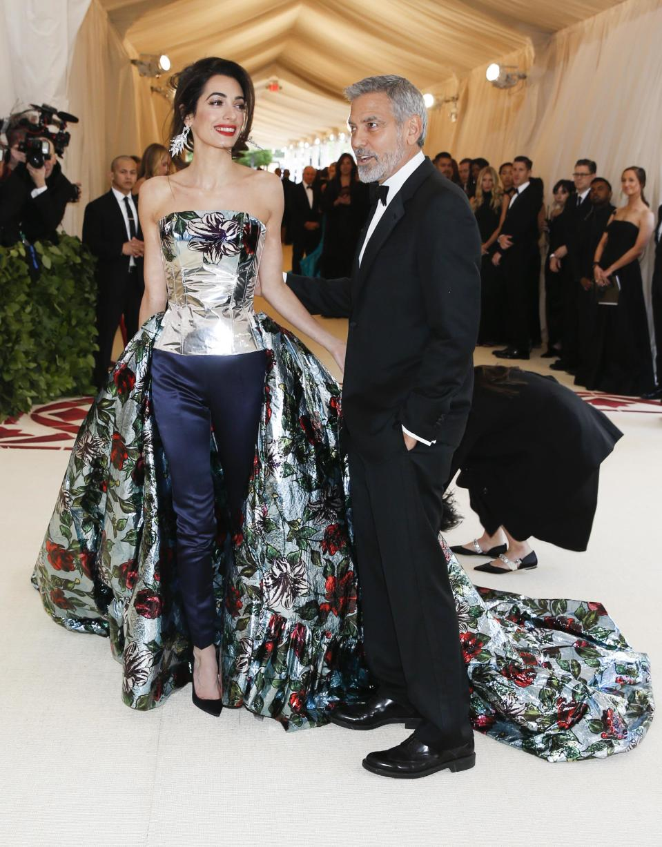 """Actor George Clooney and his wife Amal Clooney arrive at the Metropolitan Museum of Art Costume Institute Gala (Met Gala) to celebrate the opening of """"Heavenly Bodies: Fashion and the Catholic Imagination"""" in the Manhattan borough of New York, U.S., May 7, 2018. REUTERS/Carlo Allegri"""