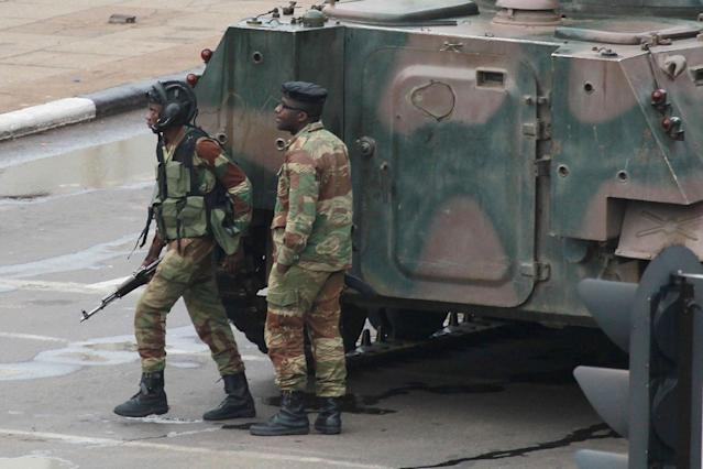 <p>Armed soldiers stand by an armored vehicle on the road leading to President Robert Mugabe's office in Harare, Zimbabwe Wednesday, Nov. 15, 2017. (Photo: Tsvangirayi Mukwazhi/AP) </p>