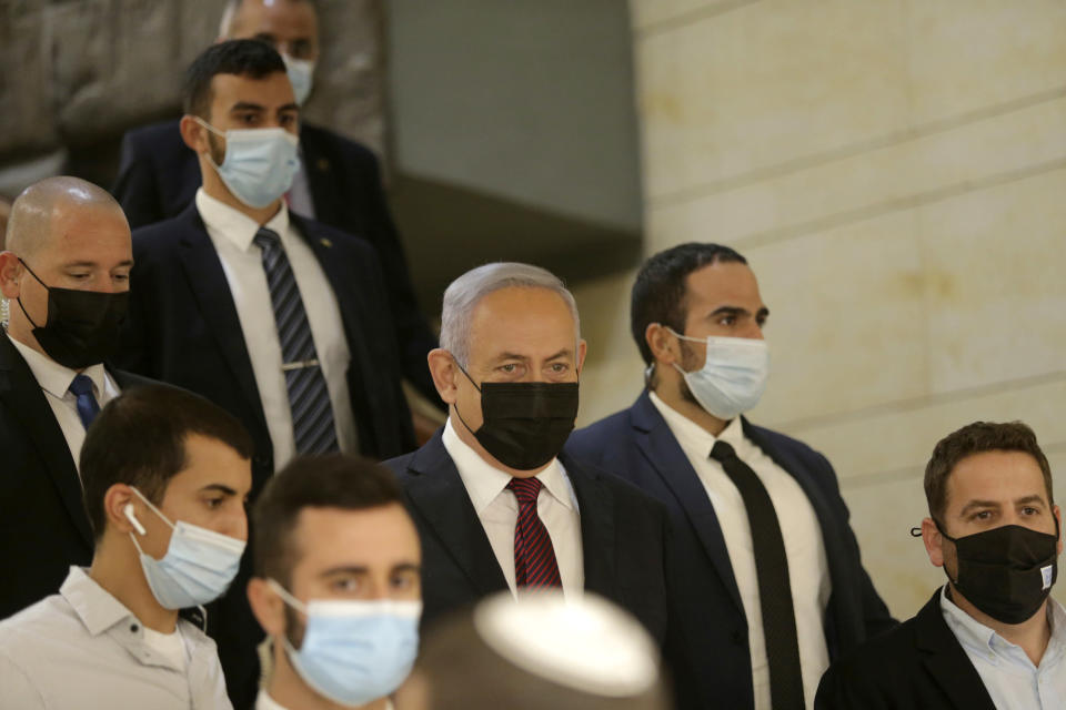 Israeli Prime Minister Benjamin Netanyahu, center, arrives at the Israeli Knesset (Parliament) ahead of a vote to dissolve the Knesset, in Jerusalem, Wednesday, Dec. 2 2020. The Israeli parliament passed a preliminary proposal to dissolve itself on Wednesday, setting up a possible fourth national election in under two years while the country is in the grip of the coronavirus pandemic.(Alex Kolomoisky/Pool via AP)
