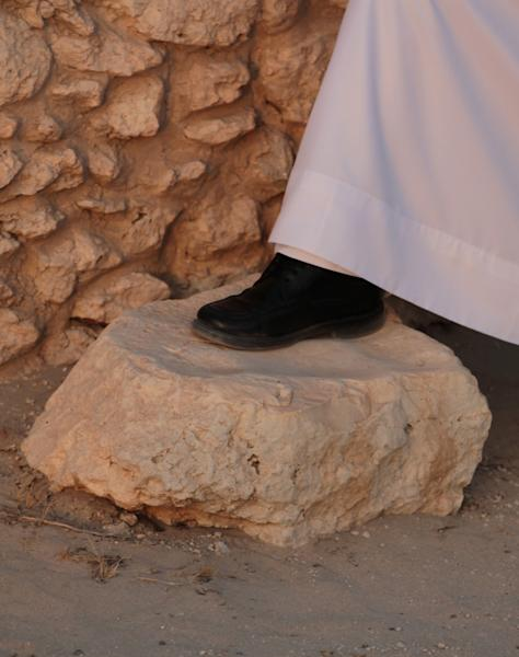 In this picture taken July 8, 2013, Bahraini archaeologist Abdul Aziz al-Suwailah rests his foot on a stone he explains was likely used by religious leaders to sit and wash themselves before entering a Dilmun-era temple in Saar, Bahrain, in the heart of an expansive Bronze-age settlement. The settlement includes the temple, which was built in about 1900 BC and remained in use for 150 to 200 years, dwellings and a honeycomb-like graveyard that stretches up to a modern highway in northwestern Bahrain. (AP Photo/Hasan Jamali)