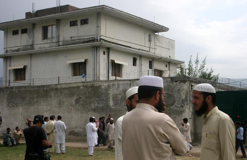 FILE - In this May 5, 2011 file photo, local residents and media are seen outside the house where al-Qaida leader Osama bin Laden was caught and killed in Abbottabad, Pakistan.  Local residents say Pakistan has started to demolish the compound in the northwest city of Abbottabad where Osama bin Laden lived for years and was killed by U.S. commandos. Two residents say the government brought in three mechanized backhoes Saturday, Feb. 25, 2012,  and began destroying the tall outer walls of the compound after sunset. They set up floodlights to carry out the work.  (AP Photo/Aqeel Ahmed, File)