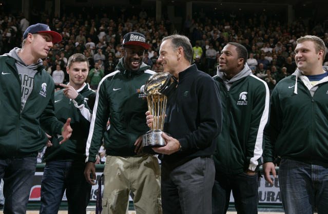 Michigan State football coach Mark Dantonio holds the 100th Rose Bowl championship trophy during halftime at an NCAA college basketball game between Michigan State and Ohio State, Tuesday, Jan. 7, 2014, in East Lansing, Mich. (AP Photo/Al Goldis)