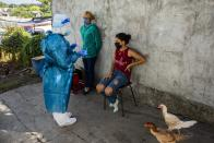 A healthcare worker prepares to test a teenager for COVID-19, on the outskirts of Montevideo, Uruguay, Thursday, March 18, 2021. Uruguay is facing a steep rise in new coronavirus infections. (AP Photo/Matilde Campodonico)
