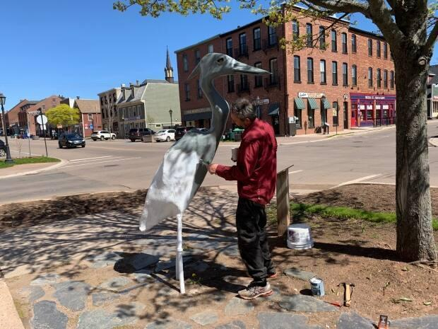 P.E.I. artist Ahmon Katz puts a fresh coat of paint on his blue heron sculpture on the corner of Queen and Water streets in Charlottetown Sunday. (Shane Ross/CBC - image credit)