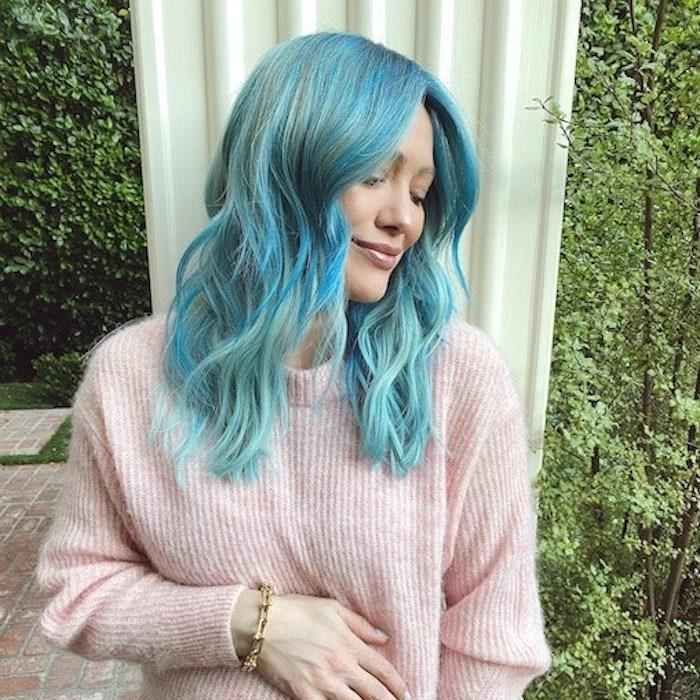 """If you're up for bleaching process that gives this cotton-candy blue shade its best results, your patience will pay off like it did for Hilary Duff. """"In order to get her hair this vibrant cotton candy blue, I had to first pre-lighten her hair with <a href=""""https://www.amazon.com/Joico-Blonde-Brightening-Shampoo-33-8-Ounce/dp/B07XRWL8PC?ots=1&slotNum=0&imprToken=78bbf04f-de13-e921-fad&tag=allure0c3-20&linkCode=w50"""" rel=""""nofollow noopener"""" target=""""_blank"""" data-ylk=""""slk:Joico's Blonde Life"""" class=""""link rapid-noclick-resp"""">Joico's Blonde Life</a>,"""" Lee <a href=""""https://www.allure.com/story/hilary-duff-cotton-candy-blue-hair-at-home-how-to?mbid=synd_yahoo_rss"""" rel=""""nofollow noopener"""" target=""""_blank"""" data-ylk=""""slk:previously told Allure"""" class=""""link rapid-noclick-resp"""">previously told <em>Allure</em></a><em>,</em> explaining that it took what felt like hundreds of foils to fully cover the actor's head. """"After processing, we did a quick pre-tone to kick out any unwanted yellow before applying the blue; this was an important step as the blue mixed with yellow could've gone green."""" Lee used <a href=""""https://www.walmart.com/ip/Joico-Vero-K-Pak-Color-Intensity-Semi-Permanent-Hair-Color-Color-True-Blue/590469456"""" rel=""""nofollow noopener"""" target=""""_blank"""" data-ylk=""""slk:Joico's Color Intensity True Blue"""" class=""""link rapid-noclick-resp"""">Joico's Color Intensity True Blue</a>, <a href=""""https://www.walmart.com/ip/Joico-COLOR-INTENSITY-Semi-Permanent-Hair-Color-Dye-Haircolor-Mermaid-Blue/901630232"""" rel=""""nofollow noopener"""" target=""""_blank"""" data-ylk=""""slk:Mermaid Blue"""" class=""""link rapid-noclick-resp"""">Mermaid Blue</a>, and <a href=""""https://www.joico.com/pro-color/color-intensity/"""" rel=""""nofollow noopener"""" target=""""_blank"""" data-ylk=""""slk:Peacock Green"""" class=""""link rapid-noclick-resp"""">Peacock Green</a> to achieve the color, followed by a deep-conditioning treatment with <a href=""""https://www.incommonbeauty.com/pages/crystal-cashmere"""" rel=""""nofollow noopener"""" target=""""_blank"""" data-ylk=""""slk:In Common'"""