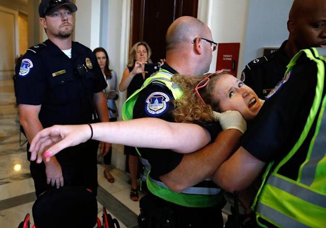 <p>Stephanie Woodward, of Rochester, NY, who has spina bifida and uses a wheelchair, is removed from a sit-in at Senate Majority Leader Mitch McConnell's office as she and other disability rights advocates protest proposed funding caps to Medicaid, Thursday, June 22, 2017, on Capitol Hill in Washington. (Photo: Jacquelyn Martin/AP) </p>