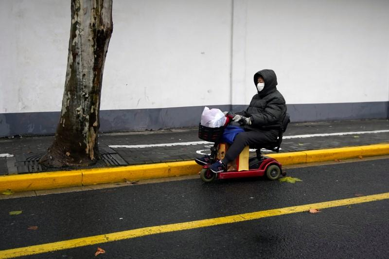 A woman wearing a protective mask is seen on a street in Shanghai