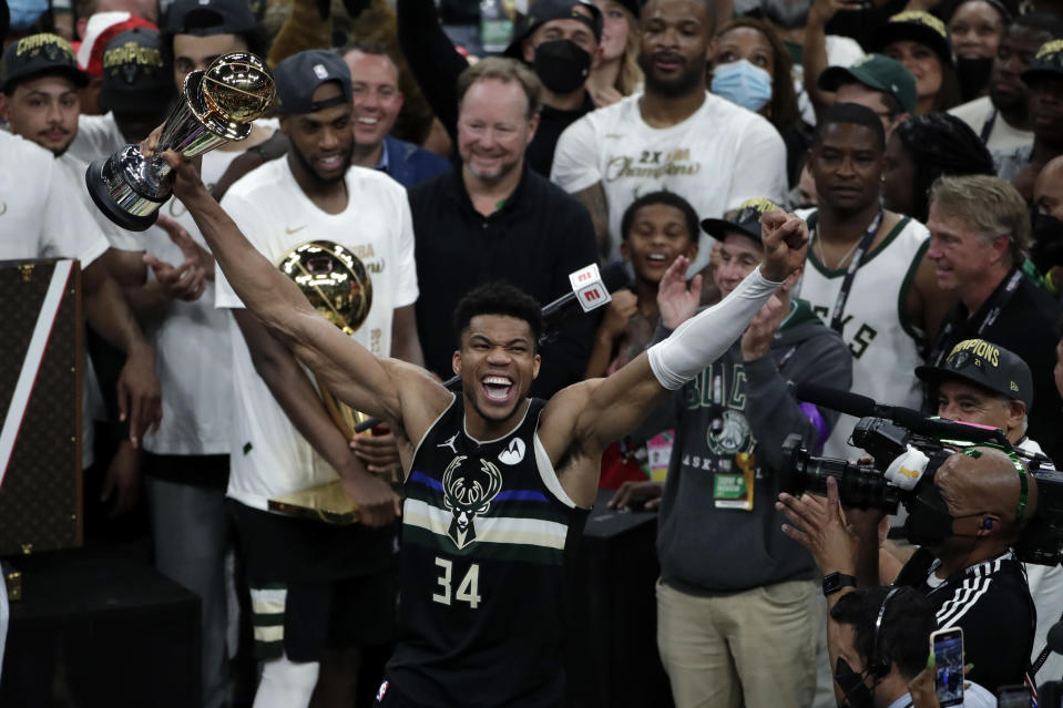 Milwaukee Bucks forward Giannis Antetokounmpo (34) celebrates with the MVP trophy, as teammates hold the championship trophy, after defeating the Phoenix Suns in Game 6 of basketball's NBA Finals Tuesday, July 20, 2021, in Milwaukee. The Bucks won 105-98. (AP Photo/Aaron Gash)