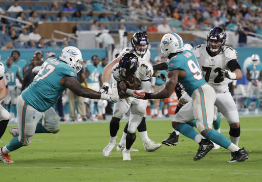 Baltimore Ravens quarterback Robert Griffin III (3) is sacked by Miami Dolphins defensive tackle Jordan Phillips (97) and defensive end Robert Quinn (94) during the first half of a preseason NFL football game, Saturday, Aug. 25, 2018, in Miami Gardens, Fla. (AP Photo/Lynne Sladky)