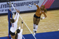 Texas' Asjia O'Neal (7) scores a point against Wisconsin's Molly Haggerty (23) and Danielle Hart (18) in the first set during a semifinal in the NCAA women's volleyball championships Thursday, April 22, 2021, in Omaha, Neb. (AP Photo/John Peterson)