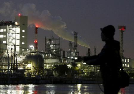 FILE PHOTO - Smoke is emitted from a chimney as a man fishes at the Keihin industrial zone in Kawasaki