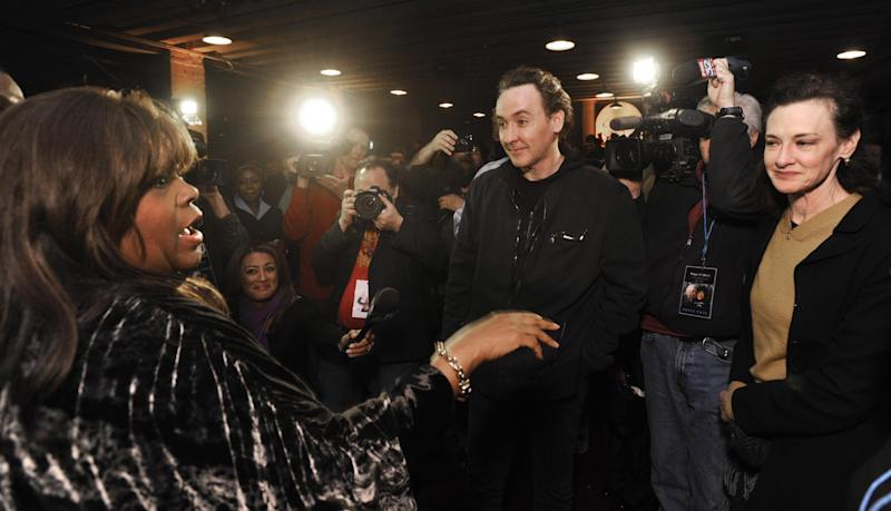 Roger Ebert's wife Chaz Ebert, left, speaks with actors John Cusack center, and Joan Cusack, right, at The Chicago Theater before a memorial for the film critic Ebert in Chicago, Thursday, April 11, 2013. The Pulitzer Prize winning critic died last week at the age of 70 after a long battle with cancer. (AP Photo/Paul Beaty)