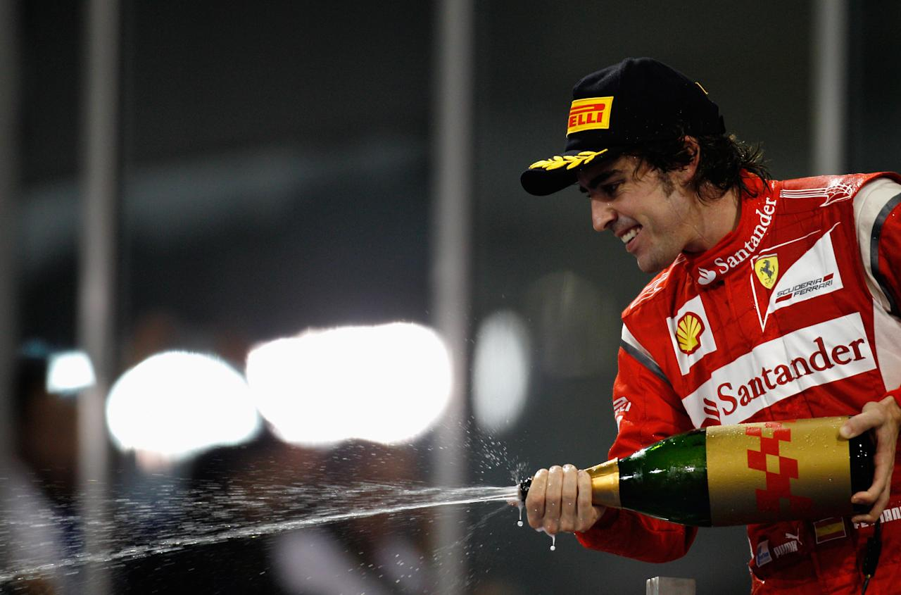 ABU DHABI, UNITED ARAB EMIRATES - NOVEMBER 13: Fernando Alonso of Spain and Ferrari celebrates on the podium after finishing second during the Abu Dhabi Formula One Grand Prix at the Yas Marina Circuit on November 13, 2011 in Abu Dhabi, United Arab Emirates. (Photo by Paul Gilham/Getty Images)