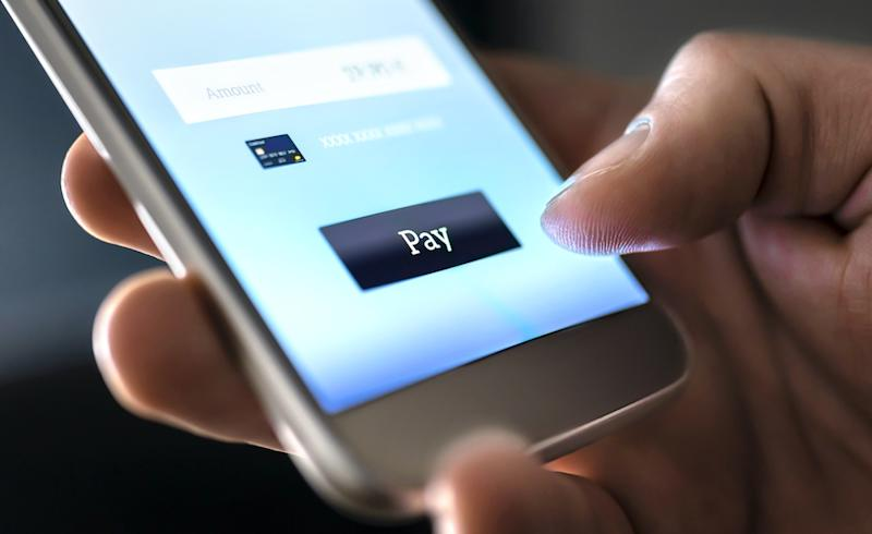 Mobile payment with wallet app and wireless nfc technology. Man paying and shopping with smartphone application and credit card information.