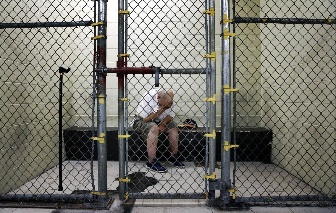 In this June 26, 2014 photo, a U.S. veteran with post-traumatic stress sits in a segregated holding pen at the Cook County Jail after he was arrested on a narcotics charge in Chicago. The Chicago complex, with more than 10,600 inmates, is one of the country's largest single-site jails. From big cities to rural counties, the nation's 3,300 local jails have turned into treatment centers of last resort for people with serious mental illnesses, most arrested for non-violent crimes. (AP Photo/Charles Rex Arbogast)