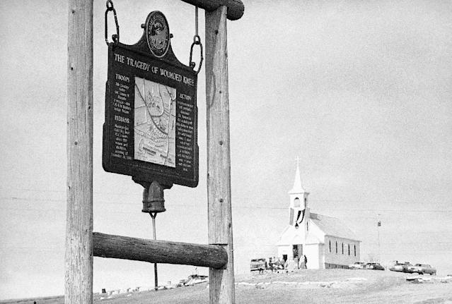 FILE - This undated file photo shows the historical marker commemorating the Wounded Knee Massacre of 1890 on the road near the Sacred Heart Catholic Church in Wounded Knee, S.D. Wednesday is the final day a landowner has given the Oglala Sioux Tribe to make an offer to buy a portion of the Wounded Knee National Historic Landmark. James Czywczynski has said he would sell the land, which sits next to where about 150 of the 300 Lakota men, women and children killed by the 7th Cavalry in 1890 are buried, and another piece of land for no less than $4.9 million. Tribal members have said the asking price is much too high. (AP Photo/File)
