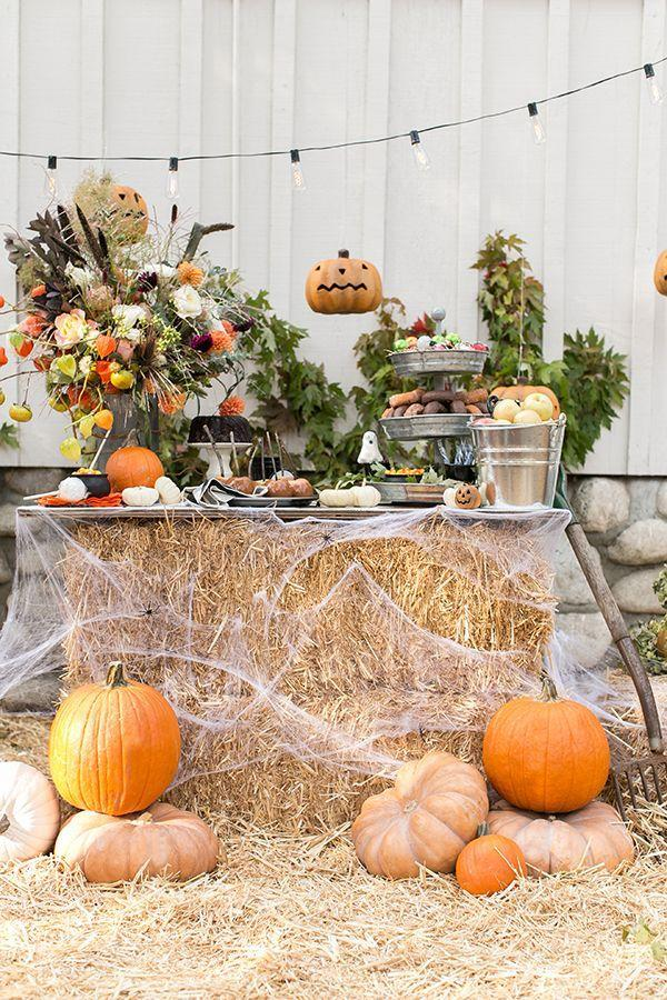 """<p>We love the idea of including hay in this year's outdoor Halloween setup for the ultimate rustic-chic look. Here's the best part: This buffet doubles as a socially distanced treat pick-up station.</p><p><strong>Get the tutorial at <a href=""""https://sugarandcharm.com/a-charming-and-traditional-halloween-party"""" rel=""""nofollow noopener"""" target=""""_blank"""" data-ylk=""""slk:Sugar and Charm"""" class=""""link rapid-noclick-resp"""">Sugar and Charm</a>.</strong></p><p><strong><a class=""""link rapid-noclick-resp"""" href=""""https://go.redirectingat.com?id=74968X1596630&url=https%3A%2F%2Fwww.walmart.com%2Fip%2FHalloween-Artificial-Pumpkin-Simulation-Fake-Lifelike-Props-Garden-Home-Decor%2F371789666&sref=https%3A%2F%2Fwww.thepioneerwoman.com%2Fholidays-celebrations%2Fg32894423%2Foutdoor-halloween-decorations%2F"""" rel=""""nofollow noopener"""" target=""""_blank"""" data-ylk=""""slk:SHOP FAUX PUMPKINS"""">SHOP FAUX PUMPKINS</a><br></strong></p>"""