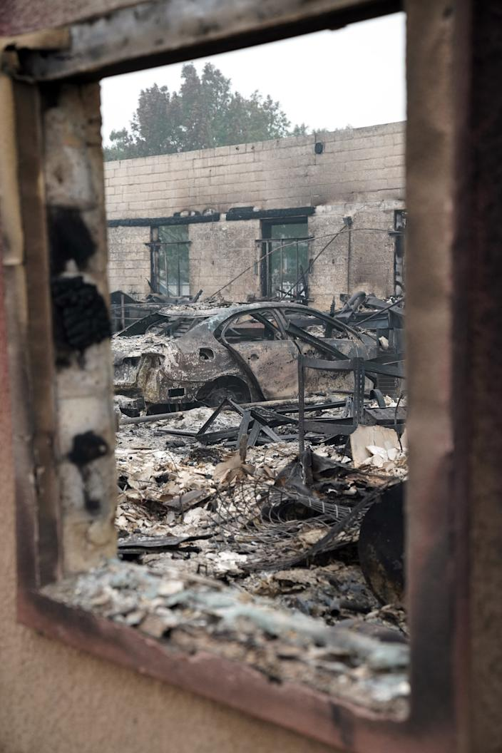 Charred vehicles sit inside a burned auto-repair shop outside Medford, Ore., following the passage of the Almeda fire.