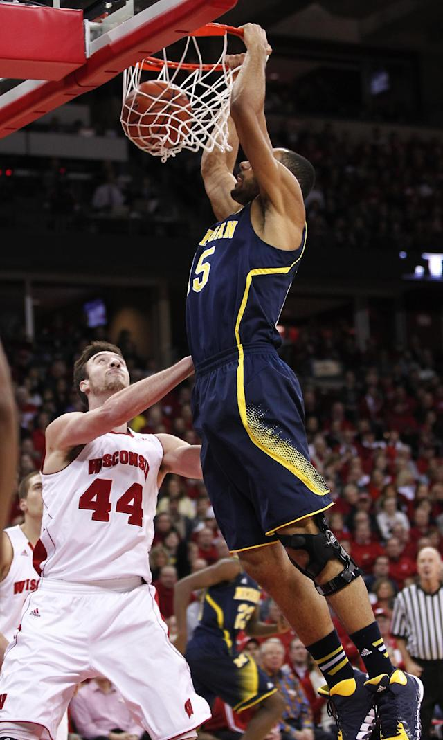 Michigan's Jon Horford, right, dunks over Wisconsin's Frank Kaminsky during the first half of an NCAA college basketball game Saturday, Jan. 18, 2014, in Madison, Wis. (AP Photo/Andy Manis)