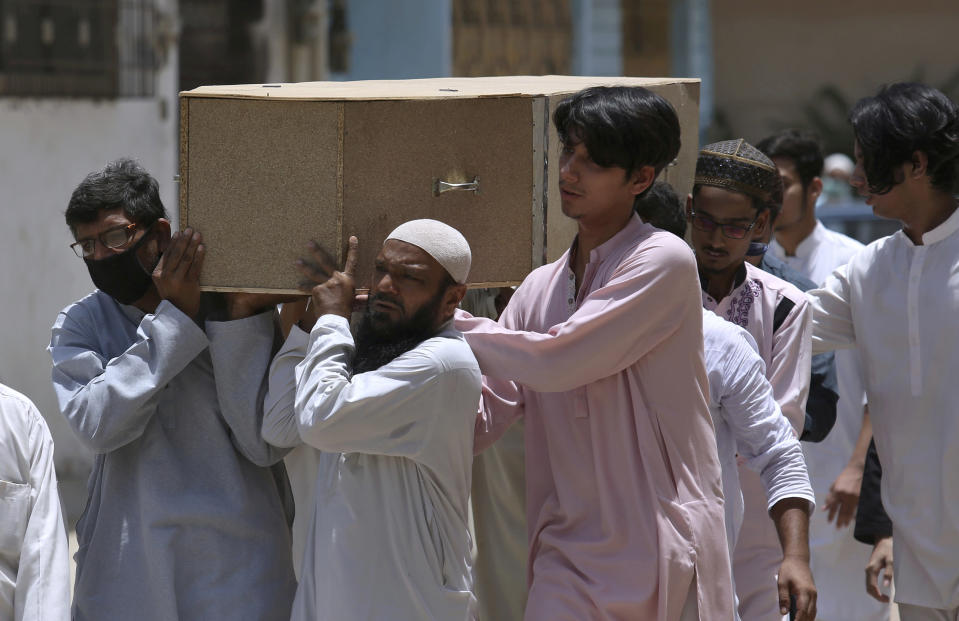 People carry the casket of a victim of Friday's plane crash, for funeral prayers in Karachi, Pakistan, Saturday, May 23, 2020. An aviation official says a passenger plane belonging to state-run Pakistan International Airlines carrying passengers and crew has crashed near the southern port city of Karachi. (AP Photo/Fareed Khan)