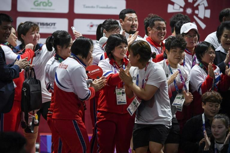North and South Korean weightlifters congratulate each other and pose for photos together at the Asian Games in Jakarta on Monday