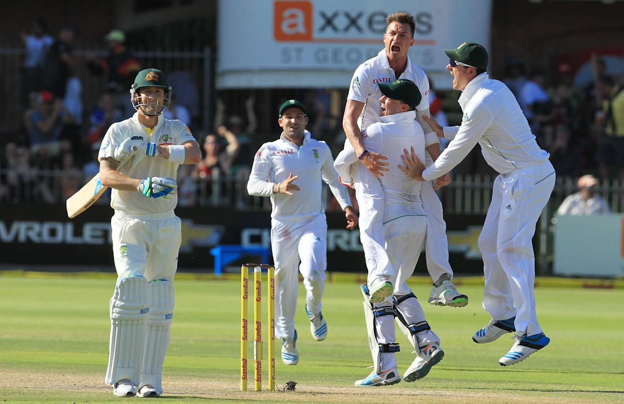 South Africa's bowler Dale Steyn, top right, celebrates with teammates after dismissing Australia's captain Michael Clarke, left, for 1 run on the fourth day of their second cricket test match at St George's Park in Port Elizabeth, South Africa, Sunday, Feb. 23, 2014. (AP Photo/ Themba Hadebe)