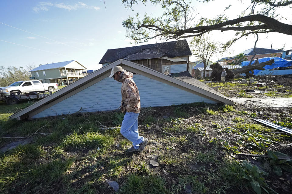 Jack Corbella walks past his neighbor's destroyed home as he assists his other neighbor who just bought the property, after the original owner decided not to rebuild, in the aftermath of Hurricane Laura and Hurricane Delta, in Grand Lake, La., Friday, Dec. 4, 2020. (AP Photo/Gerald Herbert)