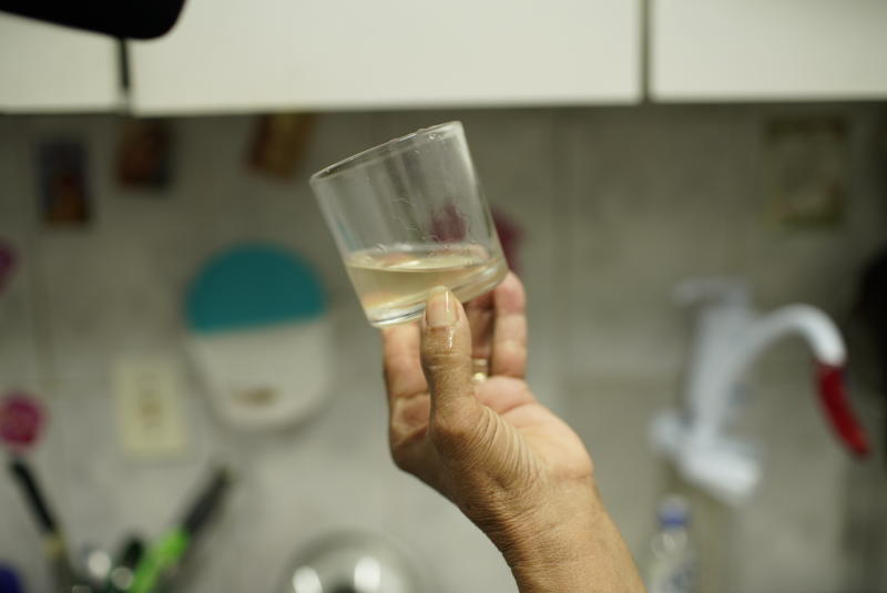 Maria Lina dos Santos shows a glass of cloudy, foul-tasting and smelling water in her home in the Complexo de Alemao slum of Rio de Janeiro, Brazil, Thursday, Jan.16, 2020. Dos Santos said cloudy water isn't unusual in her community, but police are investigating workers at a state utility after smelly tap water flowed into dozens of neighborhoods of the Brazilian city. (AP Photo/Ricardo Borges)