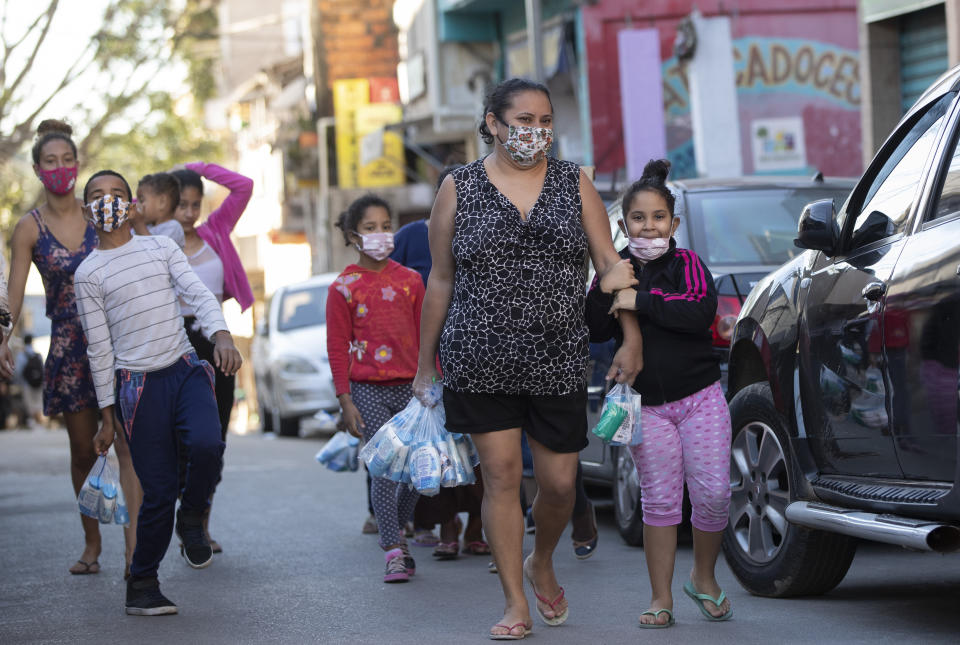 Residents return home after receiving kits equipped with cleaning products and protective face masks for children, provided by a non-governmental organization as a measure to help control the spread of the new coronavirus, in the Paraisopolis slum of Sao Paulo, Brazil, Wednesday, June 24, 2020. With over 100,000 residents, Paraisopolis is one of the areas of Sao Paulo that is most affected by COVID-19. (AP Photo/Andre Penner)