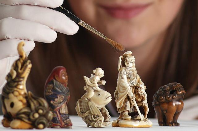 Assistant Conservator Margot Murray working on carved ivory netsuke figurines from  late 18th-early 19th century Japan