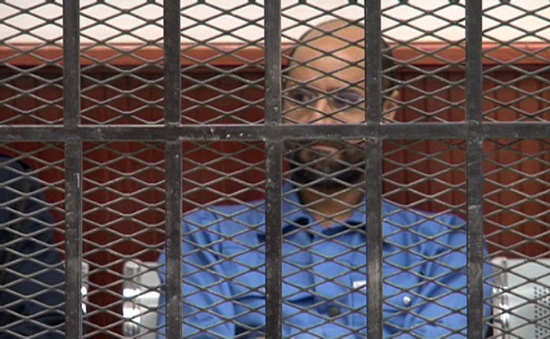 This image made from video distributed by the Zintan Media Center shows Seif al-Islam Gadhafi, center, inside a defendant's cage in a courtroom in Zintan, Libya, Thursday, May 2, 2013. The imprisoned son of Libya's slain dictator Moammar Gadhafi appeared in court on Thursday on charges of harming state security, but the judge adjourned his hearing until Sept. 19 to allow defense lawyers time to study the case.(AP Photo/Zintan Media Center)