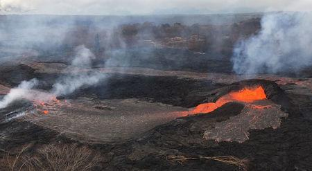 Activity at fissure 6 is seen as lava fountains build a small spatter cone (black mound) from which lava spills out on the surface and flows into a small pond (left of the cone) in Hawaii, U.S. May 25, 2018.   Picture taken May 25, 2018.    USGS/Handout via REUTERS