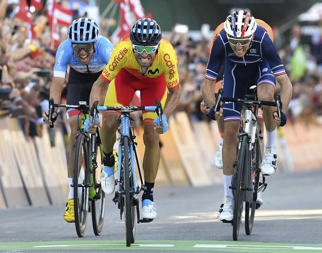 Spain's Alejandro Valverde, center, approaches the finish line to win the men's road race at the Road Cycling World Championships in Innsbruck, Austria, Sunday, Sept.30, 2018. (AP Photo/Kerstin Joensson)