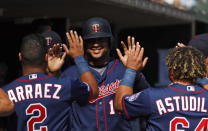 Minnesota Twins' Jonathan Schoop, center, is congratulated in the dugout after scoring in the fourth inning of a baseball game against the Detroit Tigers in Detroit, Thursday, Sept. 26, 2019. (AP Photo/Paul Sancya)