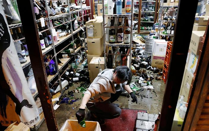 A liquor shop's manager clears the damaged bottles - Kyodo News