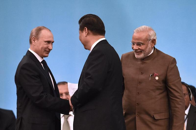Chinese President Xi Jinping (C) shakes hands with Russian President Vladimir Putin (L) and Indian Prime Minister Narendra Modi during the 6th BRICS Summit in Fortaleza, Brazil, on July 15, 2014 (AFP Photo/Yasuyoshi Chiba)