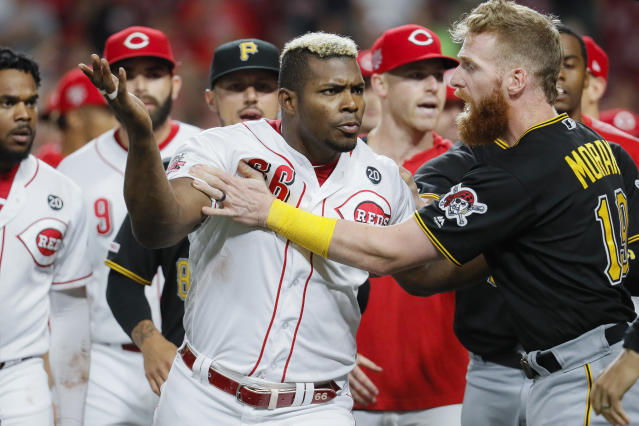 Cincinnati Reds' Yasiel Puig (66) is restrains by Pittsburgh Pirates third baseman Colin Moran (19) during the ninth inning of a baseball game Tuesday, July 30, 2019, in Cincinnati. (AP Photo/John Minchillo)
