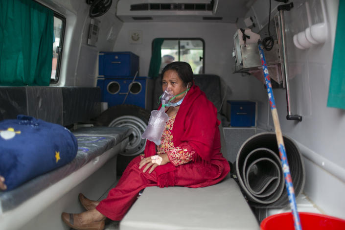 A COVID-19 patient receives oxygen in an ambulance outside an emergency ward of a hospital as she waits for a bed to be allotted at a government run hospital in Kathmandu, Nepal, Wednesday, May 12, 2021. Political turmoil has returned to Nepal, which has had eight different governments in a decade and is experiencing its worst COVID-19 surge with acute shortages of health facilities and oxygen for patients.(AP Photo/Niranjan Shrestha)