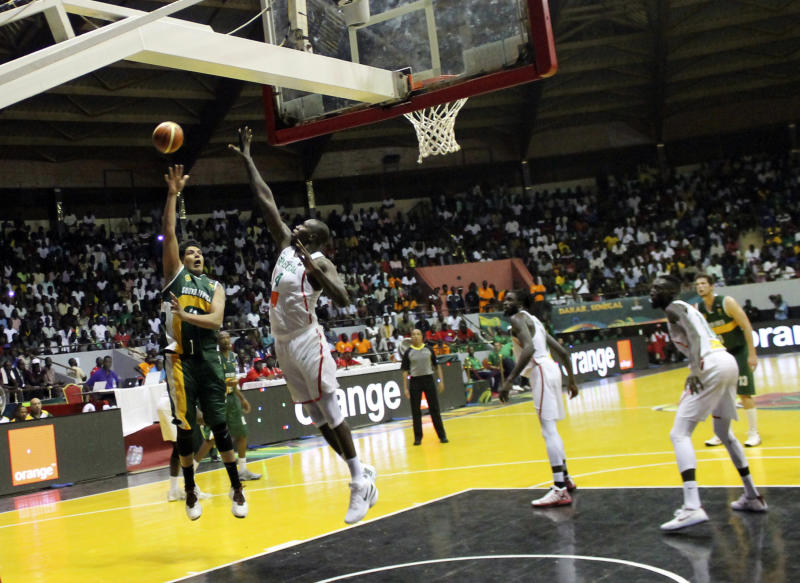 South Africa's Chris Gabriel, left, launches a hook shot during AfroBasket tournament at Marius Ndiaye stadium in Dakar, Senegal,Friday, Sept. 8, 2017. The African basketball championship may lack star power, even electrical power on occasion. But with national pride at stake, it almost always entertains. AfroBasket, which tipped off Friday in Senegal and Tunisia, can't be compared to a glitzy event like the NCAA tournament. Senegal's aging national stadium in the capital Dakar, for example, has no air conditioning. A recent women's AfroBasket game in Mali was paused because of a power cut. (AP Photo/ Ken Maguire)
