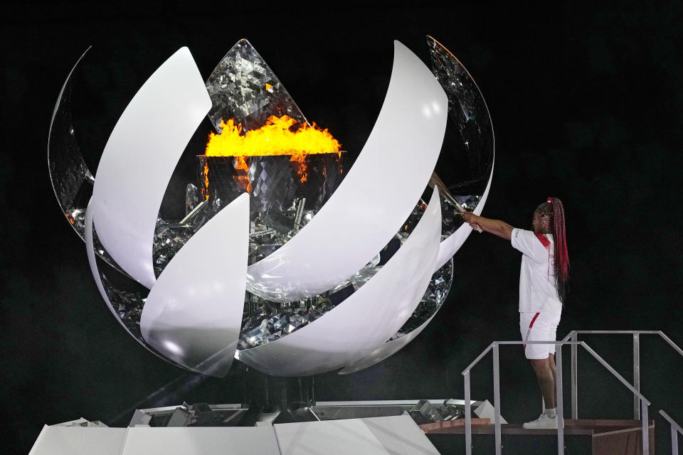 Naomi Osaka lights the Olympic flame during the opening ceremony in the Olympic Stadium at the 2020 Summer Olympics, Friday, July 23, 2021, in Tokyo, Japan. (AP Photo/David J. Phillip)