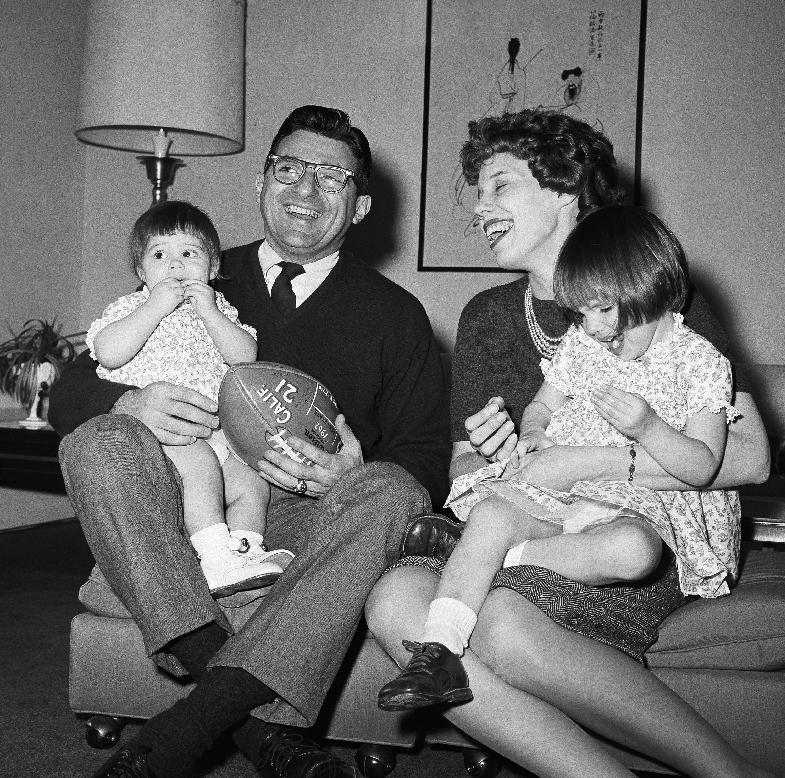 FILE - In this Feb. 16, 1966 file photo, new Penn State head football coach Joe Paterno poses with his one-year-old daughter Mary Kathryn on his lap and his wife Suzanne, with two-year-old daughter Diana Lynne, at their home in University Park, Pa. Paterno say he plans to retire at the end of the season, his long and illustrious career brought down because he failed to do all he could about an allegation of child sex abuse against a former assistant. (AP Photo/Paul Vathis, File)