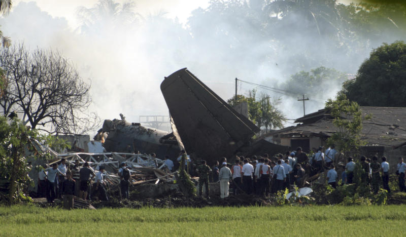 Indonesian military personnel investigate the site where an Indonesia air force plane crashed in Jakarta, Indonesia, Thursday, June 21, 2012. The Fokker F-27 turboprop plane crashed into homes in the capital Thursday during a routine training flight, killing at least six people. (AP Photo/Teguh Windharto)