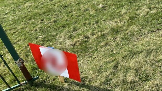 An altered paper sign that resembled a Canadian flag with the maple leaf replaced by a swastika symbol was found on the front lawn of CBC Windsor.  (CBC News - image credit)